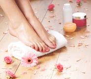 Молодая женщина добавляя сливк к ее красивым ногам Стоковое Изображение RF