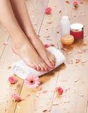 Молодая женщина добавляя сливк к ее красивым ногам Стоковые Фото