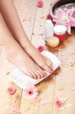 Молодая женщина добавляя сливк к ее красивым ногам Стоковое Изображение