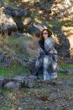 Молодая женщина обернутая в одеяле сидя на природе Стоковое Фото