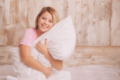 Молодая женщина обнимая подушку Стоковое Фото