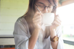 Молодая женщина оборудует белую рубашку держа кофейную чашку и выпивая co Стоковое Изображение RF