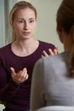 Молодая женщина обсуждая проблемы с советником Стоковые Фотографии RF