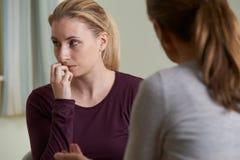 Молодая женщина обсуждая проблемы с советником Стоковое Изображение