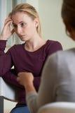 Молодая женщина обсуждая проблемы с советником Стоковые Изображения