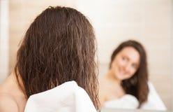 Молодая женщина обтирая волосы после ливня стоковые изображения