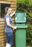 Молодая женщина около ненужного контейнера стоковое изображение rf