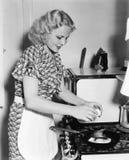 Молодая женщина ломая яичко в сковороду (все показанные люди более длинные живущие и никакое имущество не существует Warranti пос Стоковая Фотография RF