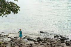 Молодая женщина оставаясь на скалистом пляже Стоковая Фотография