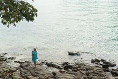 Молодая женщина оставаясь на скалистом пляже Стоковая Фотография RF