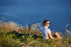 Молодая женщина ослабляет на пляже во время путешествия велосипеда Стоковое Изображение