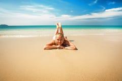 Молодая женщина ослабляет на тропическом пляже Стоковые Фото
