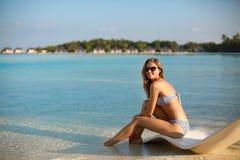 Молодая женщина ослабляя в современном шезлонге на тропическом пляже с стеклами дальше Девушка сидит на кровати солнца пляжа Стоковое Изображение RF