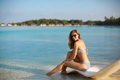 Молодая женщина ослабляя в современном шезлонге на тропическом пляже с стеклами дальше Девушка сидит на кровати солнца пляжа Стоковые Изображения