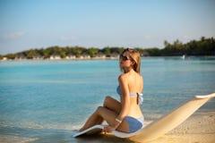 Молодая женщина ослабляя в современном шезлонге на тропическом пляже с стеклами дальше Девушка сидит на кровати солнца пляжа Стоковое фото RF
