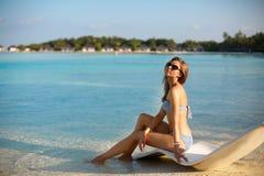Молодая женщина ослабляя в современном шезлонге на тропическом пляже с стеклами дальше Девушка сидит на кровати солнца пляжа Стоковая Фотография