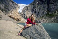 Молодая женщина ослабляя и наслаждаясь взгляд на фьорде Norwa Стоковая Фотография