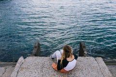 Молодая женщина ослабляя на доке и смотря вперед к морю Стоковое Изображение
