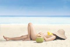 Молодая женщина ослабляя на пляже с шляпой Стоковое Изображение