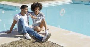Молодая женщина ослабляя с ее poolside парня Стоковое Фото