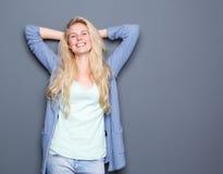Молодая женщина ослабляя с руками за головой стоковое фото