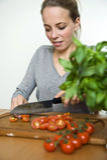 Молодая женщина отрезая свежие томаты Стоковая Фотография RF