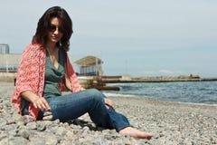 Молодая женщина отдыхая на пляже моря Стоковое фото RF