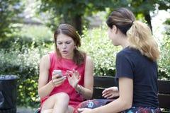 Молодая женщина отдыхая на стенде в парке Стоковое Фото
