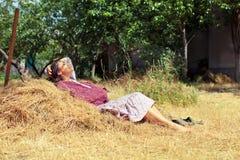 Молодая женщина отдыхая на стоге сена Стоковая Фотография RF