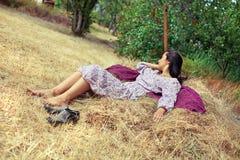 Молодая женщина отдыхая на стоге сена Стоковое Фото