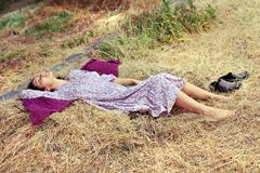 Молодая женщина отдыхая на стоге сена Стоковые Изображения