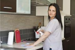 Молодая женщина очищая мебель стоковая фотография rf
