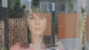 Молодая женщина очищая окно и взгляды надоели через окно сток-видео