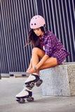 Молодая женщина одевая в rollerblading коньков идя в урбанском парке города Стоковое фото RF