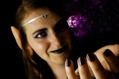 Молодая женщина одетая как эльф с polyhedral умирает стоковое изображение rf