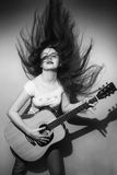 Молодая женщина одичало играя гитару черно-белую стоковые фото
