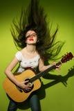 Молодая женщина одичало играя гитару Стоковое Фото