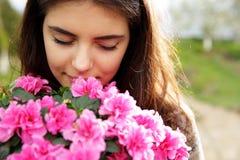 Молодая женщина пахнуть розовыми цветками стоковое фото rf
