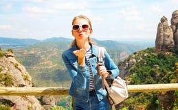 Молодая женщина перемещения посылает поцелуй воздуха на горах Стоковые Изображения