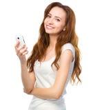 Молодая женщина печатает сообщение sms на ее телефоне стоковое изображение