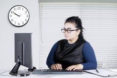 Молодая женщина печатая на клавиатуре в офисе Стоковые Изображения RF