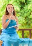 Молодая женщина писать к тетради Стоковые Изображения