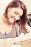 Молодая женщина пишет к черному дневнику Стоковое Изображение