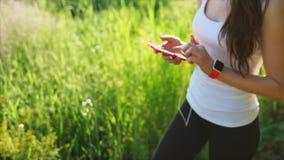 Молодая женщина пишет сообщение используя ее smartphone Предпосылка зеленой травы акции видеоматериалы