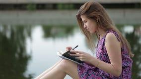 Молодая женщина пишет что-то в ее тетради на речном береге видеоматериал