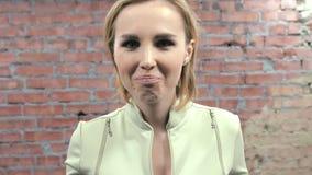 Молодая женщина показывает тоскливость, наслаждение, негодование в камере отливка Кирпичная стена сток-видео
