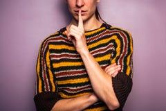 Молодая женщина показывать hush с ее пальцем на ее губе стоковое фото
