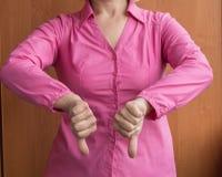 Молодая женщина показывая большие пальцы руки вниз подписывает нелюбовь, отказ, разногласие, отрицание, и конфликт Стоковая Фотография RF