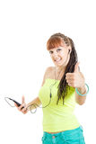 Молодая женщина показывая большой палец руки вверх слушая к музыке над наушниками стоковое изображение rf