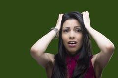 Молодая женщина показывая ей страх к кто-то над зеленым экраном который может быть заменен любой предпосылкой стоковые изображения